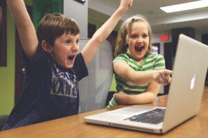starší děti jásají u počítače